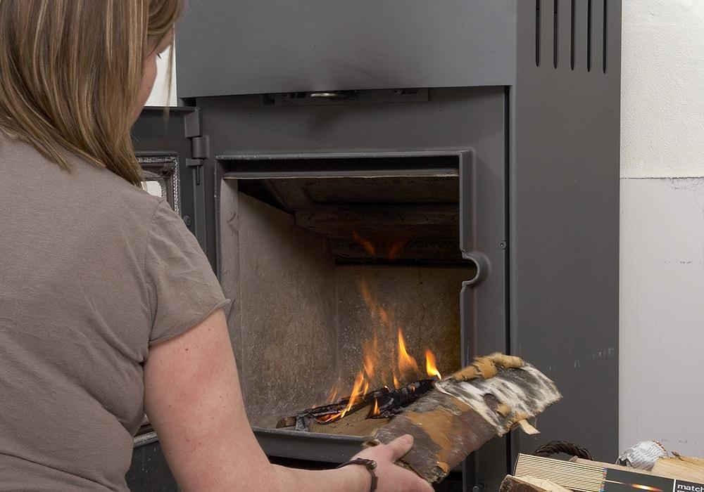 adding wood to a fireplace